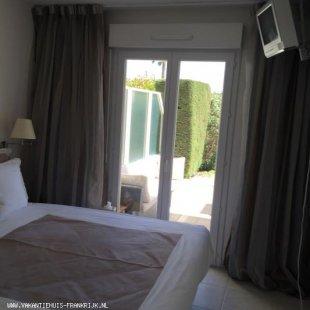 Slaapkamer met openslaande deuren naar het zonneterras In de slaapkamer een mobiel airco apparaat
