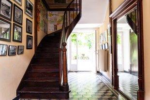 De Entrée van het huis met trap naar de verdieping en deur naar terras en tuin. De entree van het huis. De trap en de originele tegels uit de tijd van de kurkfabrikant. Deur naar terras en tuin.