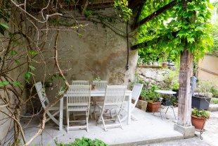 Overdekt gedeelte van het terras Hier werd vroeger de kurk gekookt. nu staat er een eettafel en 6 stoelen.