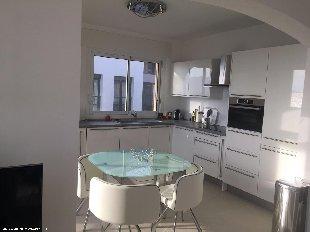 Open leuken Grote keuken met kookplaten, wasmachine, vaatwasser, magnetron-oven, koel-vrieskast en design eettafel met vier stoelen.