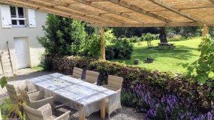 Terras met zonnescherm <br>Het is heerlijk vertoeven op het terras met een zonnescherm van riet.