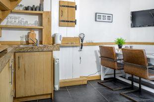 Vakantiehuis Murol woonkamer met open keuken <br>Sfeervolle woonkamer vakantiehuis Murol met eettafel en open keuken en een heerlijke leren bankstel